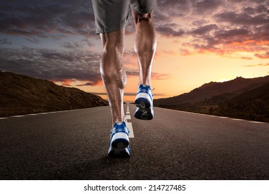 Close up of athlete's legs running on the empty road at the sunset
