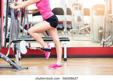 Close up of Athletic woman legs workout squats weighted lunges exercise for butt legs with suspension straps in fitness club or gym.