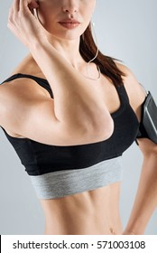Close up of athletic woman posing with headphones and smartphone