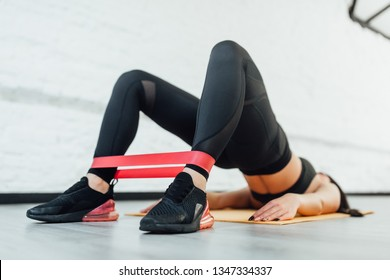 Close up of athletic woman in squat together in gym. Fit girl is exercising with resistance band for lower body relief. She is wearing sport clothes and sneakers