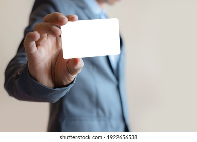 close up attractive business man holding blank white mock up card in hand.