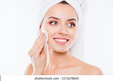 Close up of attractive charming girl with towel on her headisolated on white background touching cheek with sponge looking to the side
