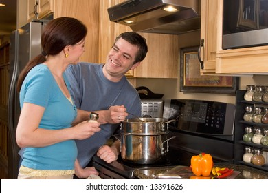 Close up of attractive couple standing in the kitchen by the stove and smiling at each other. Horizontally framed shot.
