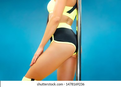 Close up of attractive female pole dance trainer at blue background. Pole dancer in sexy outfit touching pole with her buttocks. Beautiful body of athletic gymnast on blue. Exciting fitness
