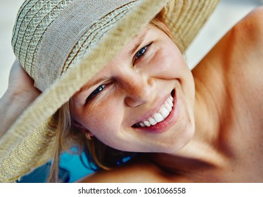 Close up of attractive female sunbathing on the beach hot summer day. Skin care, sun protection.