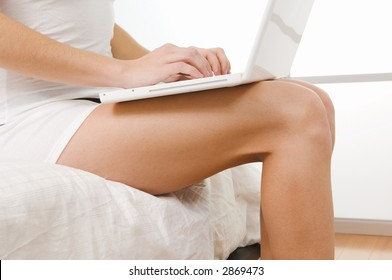 Close up of attractive girl typing on computer at end of bed in the morning.