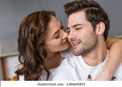 close up of attractive girlfriend kissing cheek of handsome boyfriend