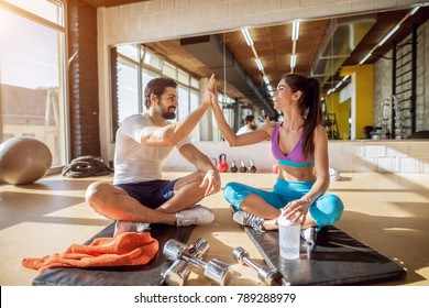 Close up of attractive pretty young fitness couple clapping hands together while sitting on the black mat and having a break in the gym in front of the mirror.