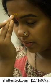 Close up of an attractive and simple Kerala/Indian/Asian girl/woman in traditional set saree and Kalamkari blouse applies prasada (turmeric powder) on forehead at temple