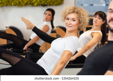 Close up of attractive and slim middle aged women who is practicing Pilates with her friends at gym. Fitness - concept of healthy lifestyle. Fitness people in the gym.
