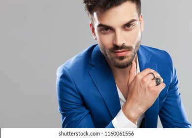 close up of attractive smart casual man smiling while sitting and leaning forward on light grey background