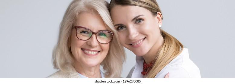 Close up attractive women faces smile look at camera, aged mother young daughter, different generations good warm relations concept horizontal banner for website header design with copy space for text