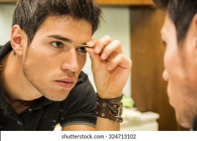 Close Up of Attractive Young Man with Dark Hair Grooming Himself - Plucking Stray Eyebrow Hairs with Tweezers While Looking into Bathroom Mirror