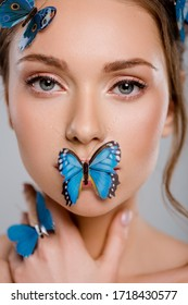 close up attractive young woman with decorative butterflies on face isolated on grey