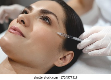 Close up of attractive young woman is getting beauty injection. Doctor is holding syringe near her eye area carefully for facelifting