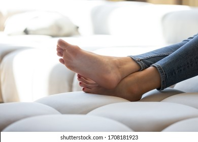 Close up attractive young woman legs lying on sofa. Beautiful female smooth foot relaxing on couch at home. Girl enjoying soft skin, foot rest and skincare cosmetics, no shoes concept.