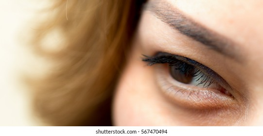 Close up of an attractive young woman looking through hair