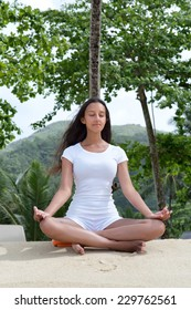 Close up Attractive Young Woman Performing Lotus Yoga Position on White Beach Sand with Closed Eyes