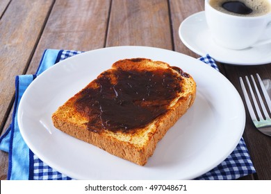 Close up of Australian breakfast with vegemite spread on a sliced wholewheat toast on a wooden table.