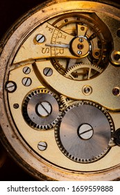 Close up of an authentic 100 hundred years old pocket watch mechanism cogs and wheels , golden