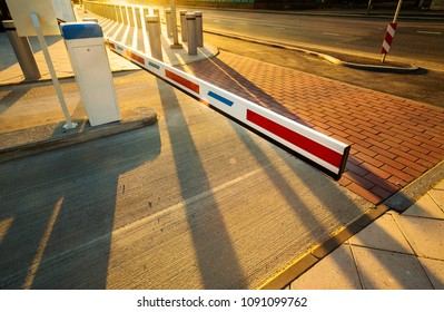 Close up of automatic boom barrier gate entrance illuminated by warm sunset light. Perspective view with long shadows