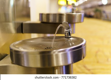 close up of automatic stainless steel public faucet with blurred airport terminal background.