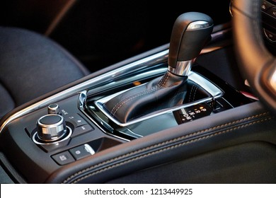 Close up of automatic transmission inside modern vehicle. Detail of luxury car interior. Trim leather gearbox and media controller. Closeup with selective focus.