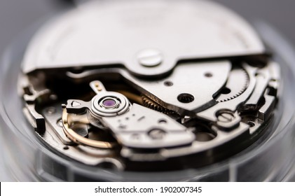 Close up of Automatic winding watch movement waiting for repairing, inside shiny japanese mechanical wristwatch parts on watchmaker table