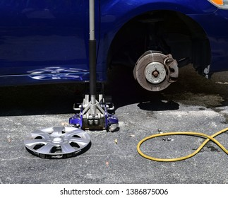 Close up of a automobile jack, hubcap, wheel drum and hydraulic hose while tire is being repaired.