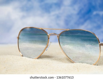 close up of aviator sunglasses in beach sand with ocean surf reflection