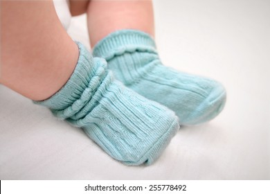 Close up of babies feet wearing blue cotton socks