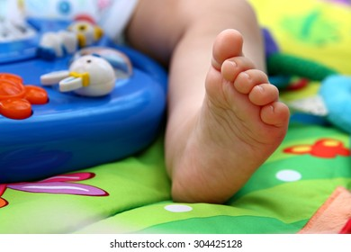 Close up of babies foot surrounded by toys