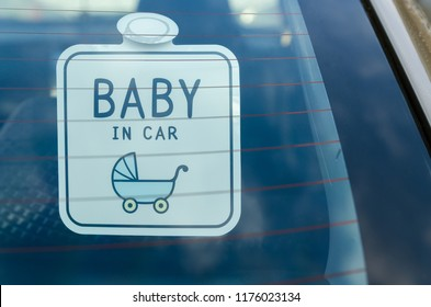 Close up of the baby in car board sign on the car back glass.