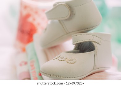 close up of baby girl elegant white shoes with warm modern colors and style during babyshower