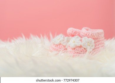 Close up Baby girl knitted shoes on white blanket background.Happy new year greeting card with copy-space. New born celebration holiday concept.