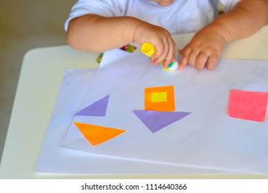 Close up baby hand make applique, glues colorful house, applying a color paper using glue stick while doing arts and crafts in preschool or home.The idea for children's creativity, art project
