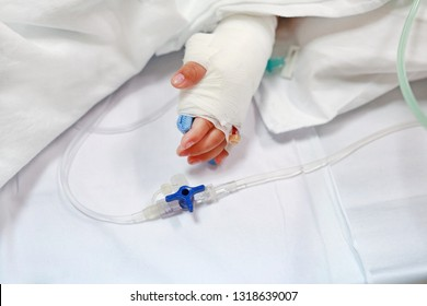 Close up baby hand on patient's bed in hospital with saline intravenous. Baby admitted at hospital. Kid patients have IV tube.