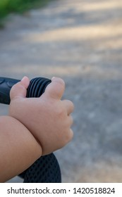 Close up of baby's hand holding on a bicycle handlebar