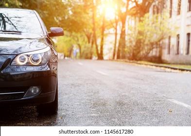 Close up back of new black sedan car parking on the asphalt road in the street