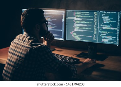 Close up back rear behind photo stubble handsome he him his guy pensive hands arms chin coder code development outsource IT processing two monitors table office wear specs formalwear plaid shirt