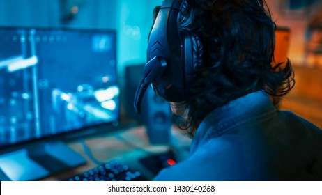 Close Up Back Shot of a Gamer Wearing a Headset with Mic and Playing Online Shooter Video Game on His Personal Computer. Room and PC have Colorful Neon Led Lights. Cozy Evening at Home.