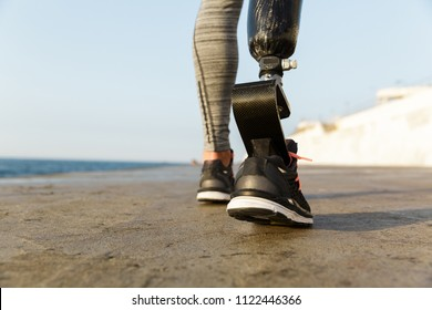 Close up back view of disabled athlete woman with prosthetic leg walking at the beach