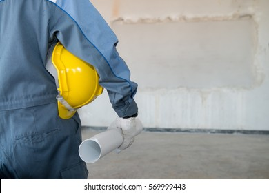 Close up back view of male construction worker holding roll of drawing and safety helmet indoor of construction site.