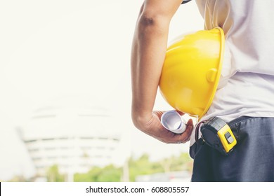 Close up back view of male construction worker holding roll of drawing and safety helmet outdoor of construction site.copy space.