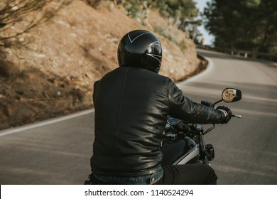 Close up back view of man in black clothes riding an American classic motorcycle