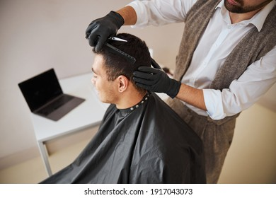 Close up back view portrait of unrecognized man with dark hair sitting in the chair while barber cutting his hair with comb and scissors