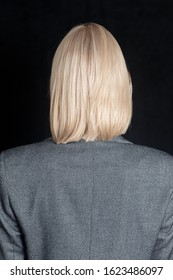 A close up back view side shot of a blonde woman with fair blunt bob hairstyle, wearing gray jacket. The model is posing against the black background. Fashionable lady turned her back.