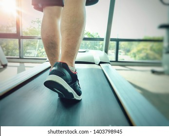 Close up back view of sports man walking or running on track treadmill machine at indoor gym in sunny day. Selective focus
