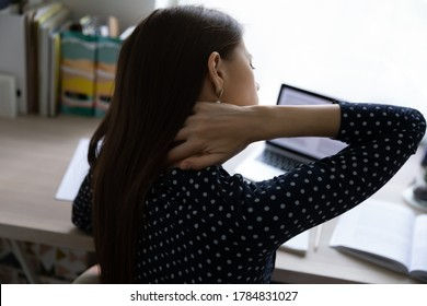 Close up back view of unhealthy young woman touch massage neck having muscular strain or spasm, unwell female sit at desk feel backache or muscle pain, tired from work, sedentary lifestyle concept