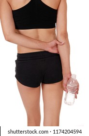 A close up of the back of a woman in black exercise outfit having a break holding the water bottle, isolated foe white background